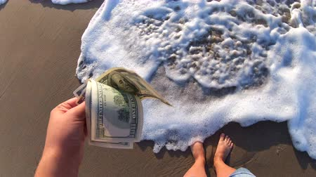 kavramak : Girl holding a money bill of 300 dollars on background of sea waves on sunny day. Hand waves sea ocean money dollars bills vacation relax sun summer. Concept holiday relax vacation. Windy wind