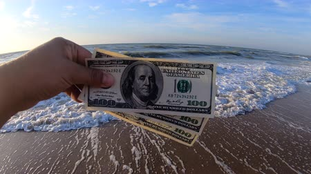 buried : Girl holding a money bill of 300 dollars on background of sea waves and sky on sunny day. Hand waves sea ocean money dollars bills vacation relax sun summer. Concept holiday relax vacation. Windy wind