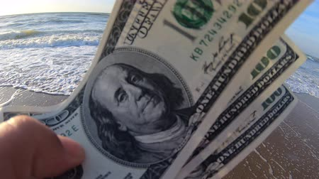 kavrama : Girl holding a money bill of 300 dollars on background of sea waves and sky on sunny day. Hand waves sea ocean money dollars bills vacation relax sun summer. Money down drain concept. Windy wind