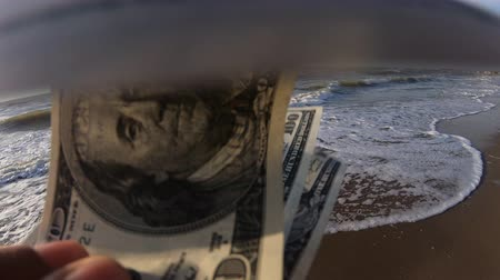 buried : Girl holding a money bill of 300 dollars on background of sea waves and sky on sunny day. Hand waves sea ocean money dollars bills vacation relax sun summer. Money down drain concept. Windy wind