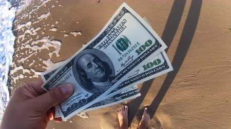kavrama : Girl holding a money bill of 300 dollars on background of sea waves on sunny day. Hand waves sea ocean money dollars bills vacation relax sun summer. Concept holiday relax vacation. Windy wind