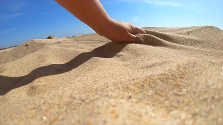 scatters : Slow motion. Low angle. Girl picks up handful of sand in her palm and sprinkles or pours it closeup. The girl scoops up sand and spills it. Womans hand scatters sand through his fingers. Stock Footage