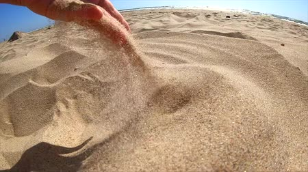 deslizamento : Slow motion. Low angle. Girl picks up handful of sand in her palm and sprinkles or pours it closeup. The girl scoops up sand and spills it. Womans hand scatters sand through his fingers. Vídeos