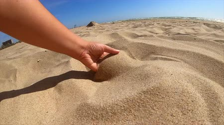 hrubý : Slow motion. Low angle. Girl picks up handful of sand in her palm and sprinkles or pours it closeup. The girl scoops up sand and spills it. Womans hand scatters sand through his fingers. Dostupné videozáznamy
