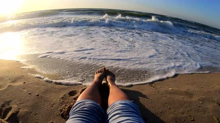 sıçramasına : Slow motion. The girl is sitting near sea and waves roll on her feet on sandy beach in bright sunny day. Concept rest relax summer recreation vacation holiday. Top view Stok Video