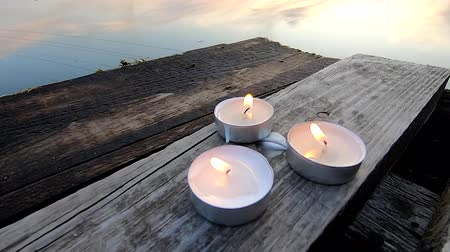 quiet evening : Three pill tablets candles lie on the edge of an old wooden vintage plank wharf on the mirrored surface of the lake water in calm, calm weather during twilight dawn sunset close-up. Mood romantic