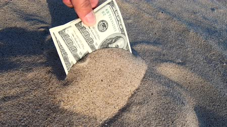 gömülü : A girl takes out from the sand money notes of three hundred dollars. Concept finance money holiday relax vacation. Sunny summer warm day. A man takes out dollars from sand buried money banknotes