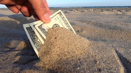 partially : A girl takes out from the sand money notes of three hundred dollars. Concept finance money holiday relax vacation. Sunny summer warm day. A man takes out dollars from sand buried money banknotes