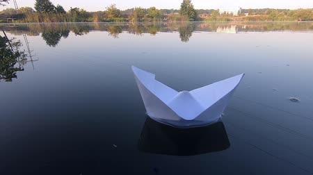 оригами : White boat floats on smooth mirror surface of pond lake in calm, sunny summer weather. A paper boat is floating in water close-up. Origami ship. Sailing. Concept of dream, future, childhood, freedom Стоковые видеозаписи