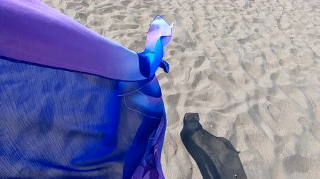 pareo : Transparent shawl in wind over sand of sea shore with dark shadow. Abstract conceptual background. Scarf cloth fluttering in wind over sand. Wave purple pink cloth satin fabric background. Slow motion