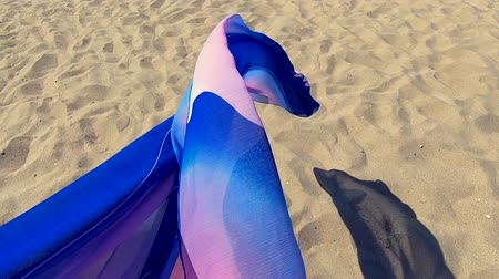折り目 : Transparent shawl in wind over sand of sea shore with dark shadow. Abstract conceptual background. Scarf cloth fluttering in wind over sand. Wave purple pink cloth satin fabric background. Slow motion