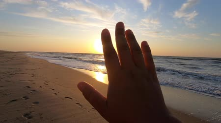 arms in the air : Slow motion. POV of hand of man who moves it in air, through fingers through rays of sun during sunrise sunset dawn on beach sea ocean. Rest relax vacation holiday. Ocean sea rest relax summer concept Stock Footage