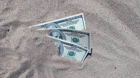 buried : Money dolars half covered with sand lie on beach close-up. Dollar bills partially buried in sand. Three hundred dollars buried in sand on sea ocean beach Concept finance money holiday relax vacation Stock Footage