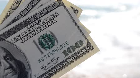 Girl holding money bill of 300 dollars on background of sea ocean waves and blue sky close-up. Hand wave sea ocean money dollars vacation. Concept finance money holiday traveling