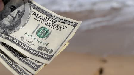Girl holding money bill of 300 dollars on background of sea ocean waves with white foam and sand wet beach with footprints in sand close-up. Concept finance money holiday traveling dollars vacation