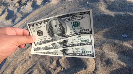 Girl holding money bill of 300 dollars on background of over sand of sea ocean sandy beach close-up. Hand wave sea ocean money dollars vacation. Concept finance money holiday traveling Wideo