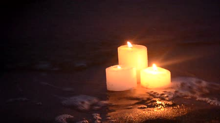 Three small yellow candles on sandy beach near sea ocean waves burning on shore at night close-up. Romance relax mood background.