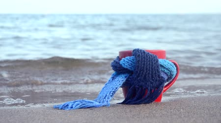 Red mug with coffee tied with blue knitted scarf stands on sandy beach of ocean sea waves. Concept warm mood travels relax ocean sea vacation holiday rest Wideo