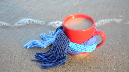 Red mug with coffee tied with blue knitted scarf stands on sandy beach of ocean sea waves on sunny day. Concept warm mood travels relax ocean sea vacation holiday rest