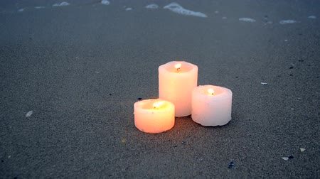 Three small yellow candles on sandy beach near blue sea ocean waves burning on shore in evening close-up. Romance relax mood background.