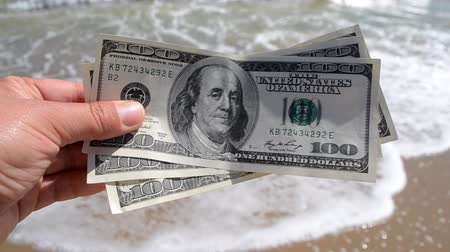 Girl holding money bill of 300 dollars on background of sea ocean waves with white foam and sand wet beach close-up. Hand wave sea ocean money dollars vacation. Concept finance money holiday traveling