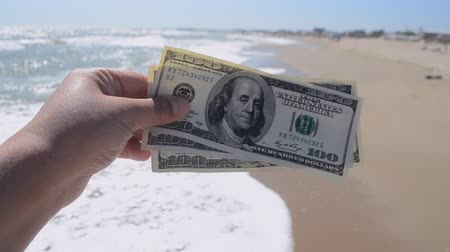 Girl holding money bill of 300 dollars on background of sea waves sand beach and sky on sunny day. Hand waves sea ocean money dollars bills vacation relax summer. Concept finance money holiday