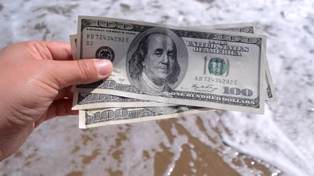 Girl holding money bill of 300 dollars on background of sea oceans waves and sand wet beach close-up on sunny day. Hand waves sea ocean money dollars vacation. Concept finance money holiday traveling Wideo