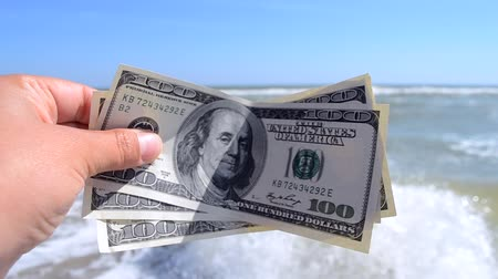 kavrama : Girl holding a money bill of 300 dollars on background of sea waves and sky on sunny day. Hand waves sea ocean money dollars bills vacation relax summer. Concept finance money holiday horizon skyline