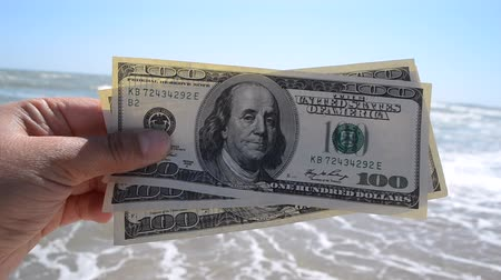 tourer : Girl holding money bill of 300 dollars on background of sea ocean waves and blue sky close-up. Hand wave sea ocean money dollars vacation. Concept finance money holiday traveling