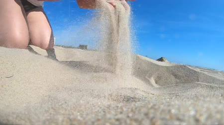 Slow motion. Low angle. Girl picks up handful of sand in her palm and sprinkles or pours it closeup. The girl scoops up sand and spills it. Womans hand scatters sand through his fingers. Vídeos