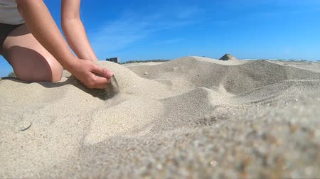 Slow motion. Low angle. Girl picks up handful of sand in her palm and sprinkles or pours it closeup. The girl scoops up sand and spills it. Womans hand scatters sand through his fingers. Wideo