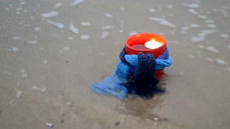 Red mug candlestick with paraffin candle tablet tied with blue knitted scarf stands on sandy beach of ocean sea waves. Concept fire romance relax mood burning background warm ocean sea holiday rest