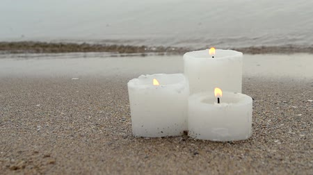 Three small white paraffin candles burning on sandy beach shore edge near blue sea ocean waves burning on shore in day close-up. Concept fire romance relax mood burning calm weather background.