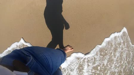 Black shadow of girl who is walking along wet sandy beach on shore of ocean sea island. Slow motion. The girl is walks near sea and waves roll on her feet on sandy beach in bright sunny day.