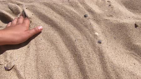 scatters : Mans hand scatters sand through his fingers. Hand movement on the sand surface, top view. Movement of the hand over the surface of the sand. Girl draws infinity sign on sand surface close-up. Stock Footage