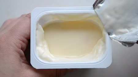 lids : A man person opening yellow yogurt close-up.