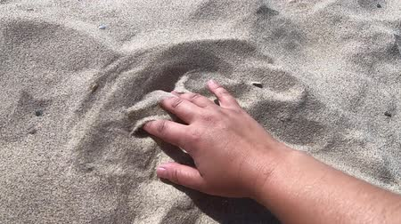 polvilha : Mans hand scatters sand through his fingers. Hand movement on the sand surface, top view. Girl draws on sand surface close-up. Sand scattering or spreading Vídeos