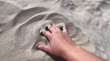 scatters : Mans hand scatters sand through his fingers. Hand movement on the sand surface, top view. Girl draws on sand surface close-up. Sand scattering or spreading Stock Footage