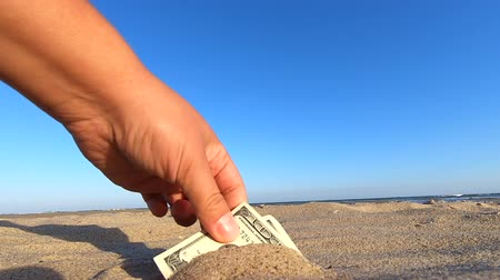 partially : A girl takes out money notes of three hundred dollars from the sand beach and blue sky. Concept finance money holiday relax vacation. A man takes out dollars from sand buried money banknotes