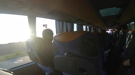 мостовая : Man looks out the window of riding bus. View from high speed bus at landscapes field and trees blue sky Traveling from car on roads and highways. Concept travels journey ride drive traveling Стоковые видеозаписи