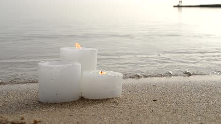 sand bank : Three small white paraffin candles burning on sandy beach shore edge near gray sea ocean waves burning on shore in day close-up. Concept fire romance relax mood burning calm weather background.