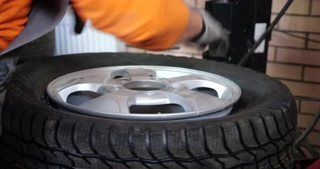 монтаж : Sservice Man put on tyre on car wheel by special tool, mechanic using mounting tool for tire repair