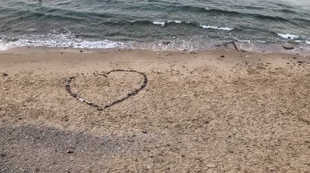 perdão : A sea wave washes into a heart made of stones on a lonely beach. Valentines Day concept, 4k video
