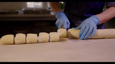 being cut up : Close up of dough being cut up into small portions. Raw dough for baking