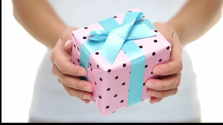 přítomný : Present or Xmas gift. Hands holding a decorative Xmas gift with pretty pink polka dot paper tied with a turquoise ribbon and bow for your Christmas greeting.