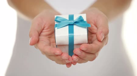 fitas : Decorative gift box tied with a turquoise ribbon and bow carefully cupped in female hands as she gives a surprise present to a loved one