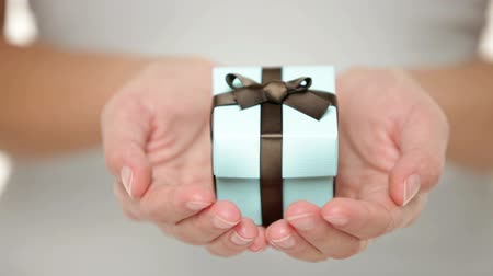 подарок : Female hands holding a small present - close up Стоковые видеозаписи