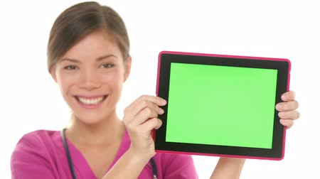 monitor počítače : Medical nurse doctor showing tablet pc computer green screen with copy space for your text or design. Mixed race Asian Chinese  Caucasian female medical professional smiling happy on white background Dostupné videozáznamy