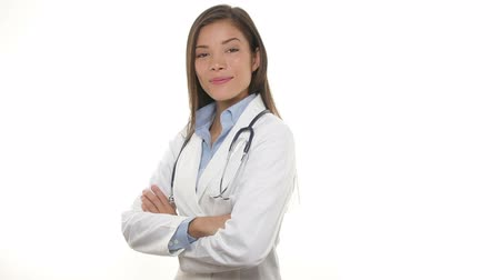 Young medical doctor woman walking in, smiling proud, crossing arms and looking at camera. Portrait of Young medical professional with stethoscope and lab coat isolated on white background. Стоковые видеозаписи