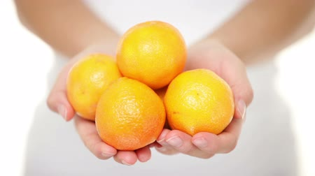 orange background : Clementine. Clementines that are a variety of mandarin oranges citrus fruits. Woman showing handful moving them into focus. Shot in studio with shallow depth of field.